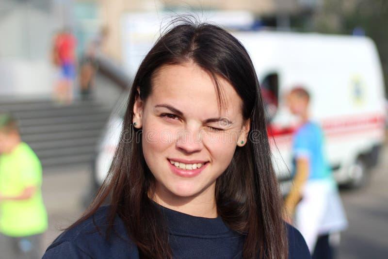 langharig donkerbruin meisje die in het vierkant op de achtergrond van een ziekenwagen glimlachen Portret van Europese vrouw in b royalty-vrije stock fotografie
