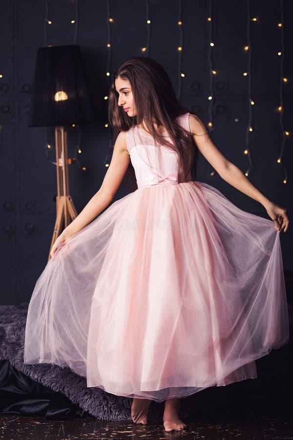Langharig meisje in roze kleding in studio op donkere achtergrond met bokeh De ruimte van het exemplaar stock fotografie