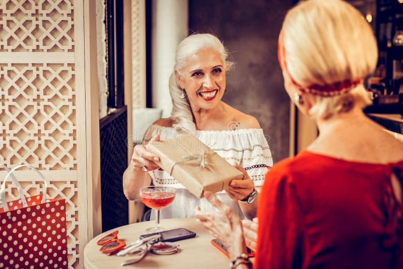Langharige dame met brede glimlach die gift in ambachtdocument nemen royalty-vrije stock afbeelding