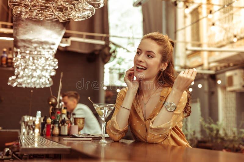 Langharige glimlachende stralende dame die van zitting genieten bij de bar royalty-vrije stock fotografie