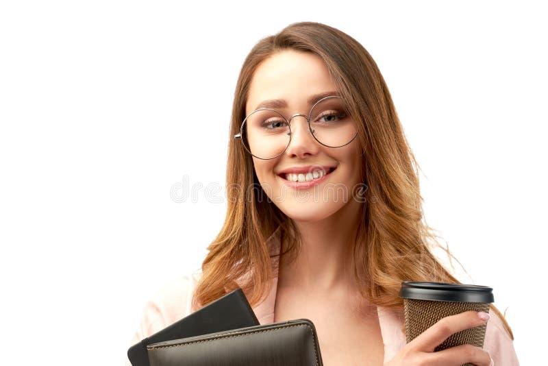 Langharige leuke glimlachende donkerbruine bedrijfsdame die een omslag met documenten en een Kop van koffie of thee houden stock fotografie