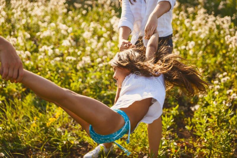 Langharige meisjesschommeling, die handen en voeten houden royalty-vrije stock foto