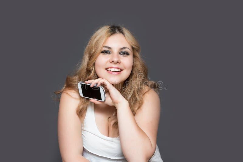 Langharige vrouw die slimme telefoon tonen bij de camera stock foto's