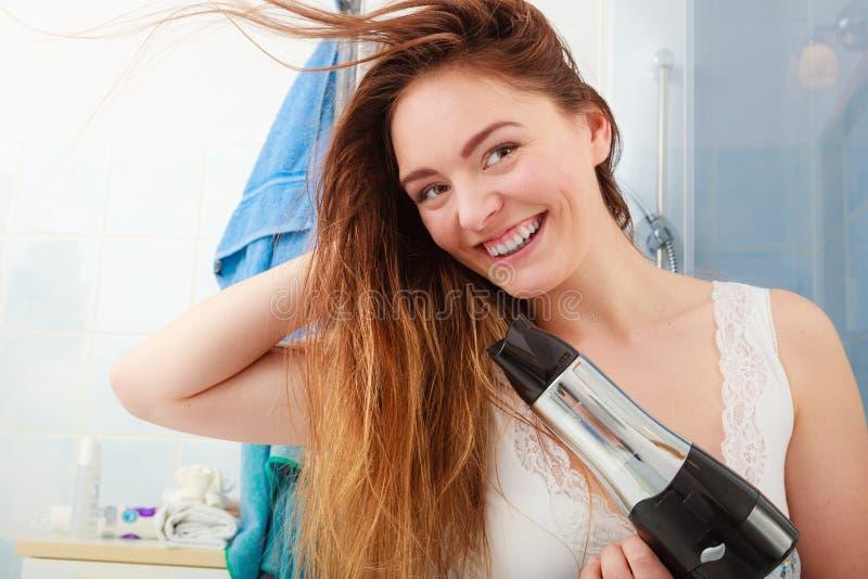 Langharige vrouwen drogend haar in badkamers stock foto's