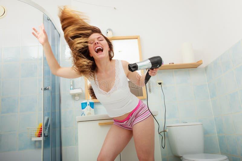 Langharige vrouwen drogend haar in badkamers royalty-vrije stock foto's