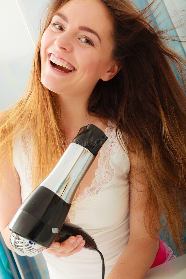 Langharige vrouwen drogend haar in badkamers haircare royalty-vrije stock fotografie
