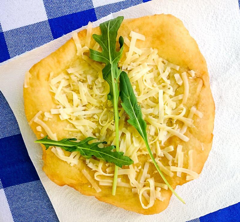 Langos calientes con queso, crema del ajo y arugula imagen de archivo