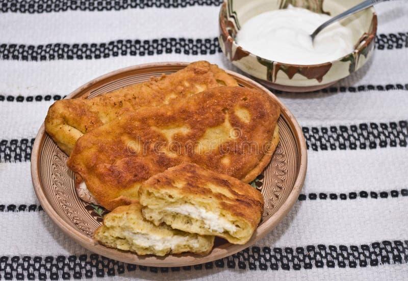 Langos (pasta fritta - ciambelle) ha riempito di formaggio salato immagini stock