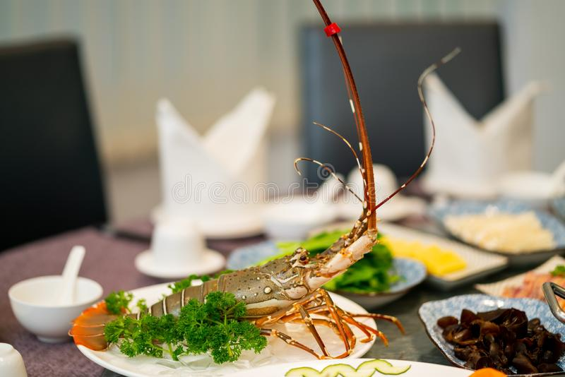 Langosta con perejil en una placa blanca redonda cerca de otros platos en el fondo imágenes de archivo libres de regalías