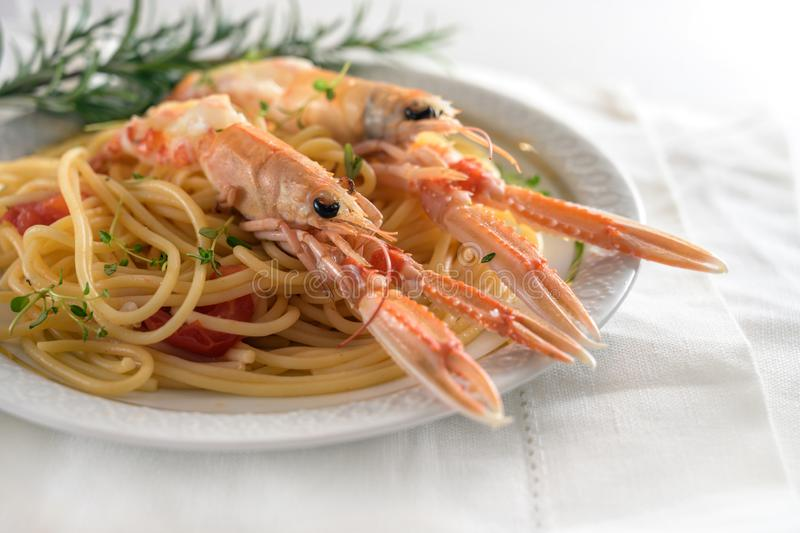 Langoustine, also called scampi or Norway Lobster, on a Mediterranean spaghetti meal with tomatoes, garlic, parmesan cheese and stock photography