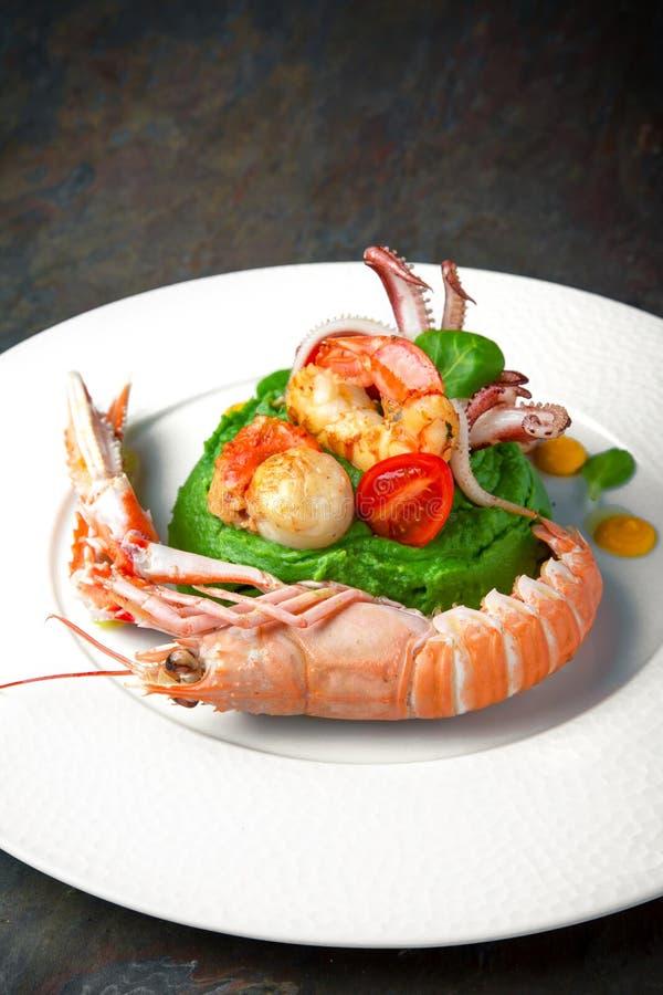 Langoustine, kammossel, octopus en mosselen met spinaziepuree Italiaans restaurant menu royalty-vrije stock afbeeldingen