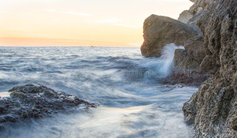 Langsame Belichtungszeitgefangennahme der Wellen, die auf Felsen, kroatisch zerstoßen stockfotos