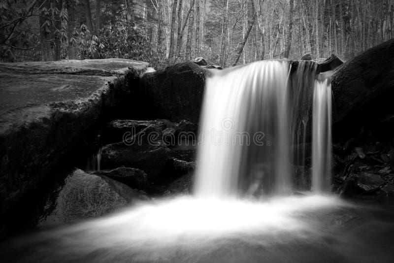 Langsames Belichtungszeit-Naturfotografie eines Wasserfalls mit Moss Covered Stones stockfoto