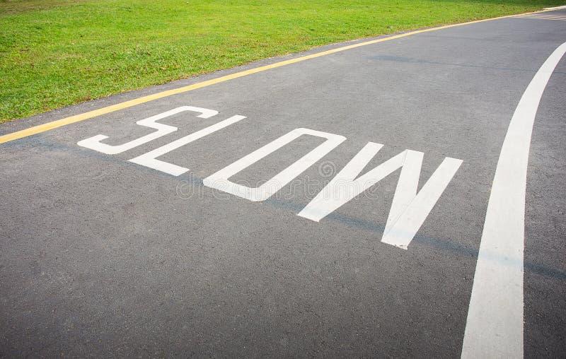 Langsames Zeichen gemalt auf der Straße stockbild