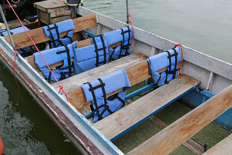 Langschwänzige Boote der Nahaufnahme auf Fluss mit dem Schwimmwestehängen stockfotos