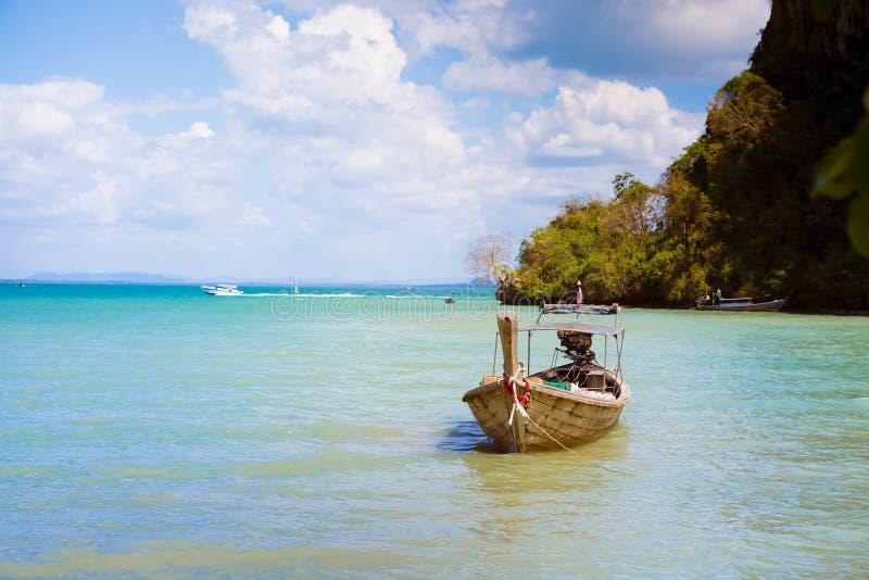 Langschwänziges Boot mit Produkten und Waren Festgemacht am Ufer auf einem tropischen sandigen Strand Vor dem hintergrund des bla stockbilder