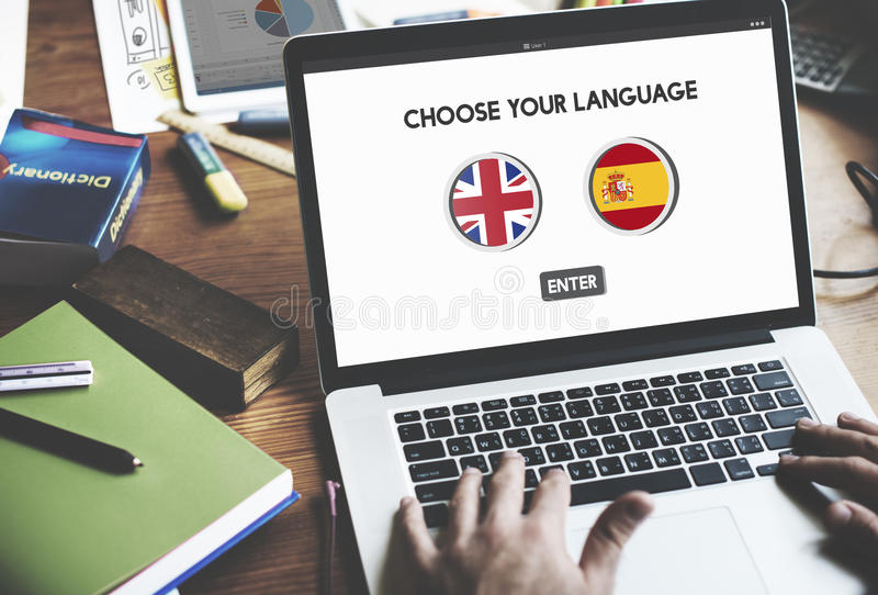 Language Dictionary English Spanish Concept. Men's hand typing on notebook with English Spanish dictionary screen stock image