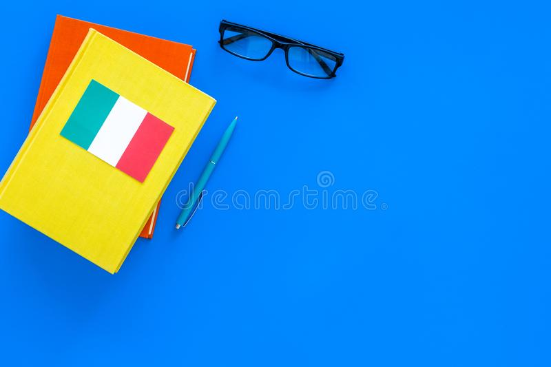 Language study concept. Textbooks or dictionaries of foreign language near italian flag on blue backgrond top view copy stock images
