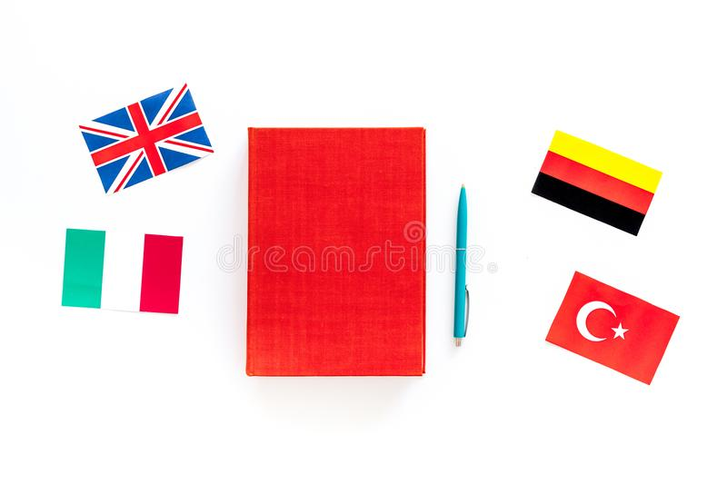 Language study concept. Textbooks or dictionaries of foreign language near flags on white backgrond top view royalty free stock image