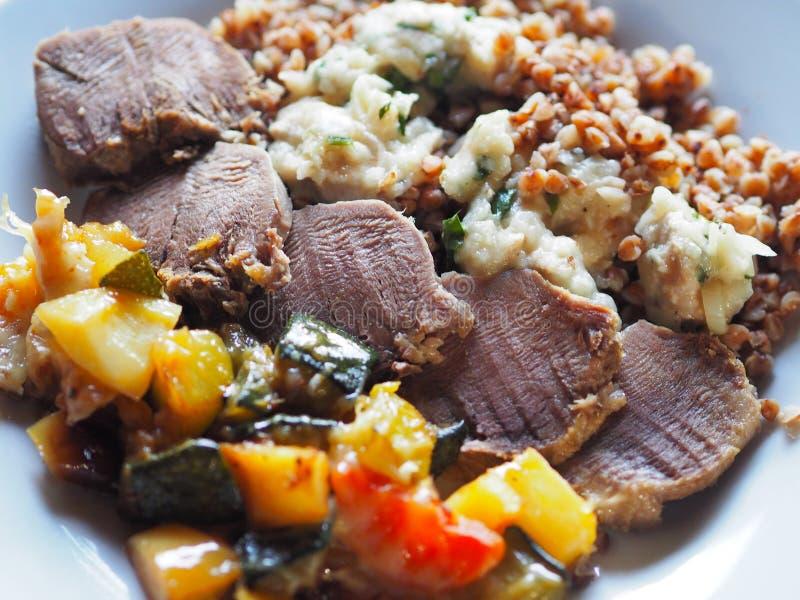 Langue bouillie avec la garniture et légumes dans un plat photographie stock libre de droits