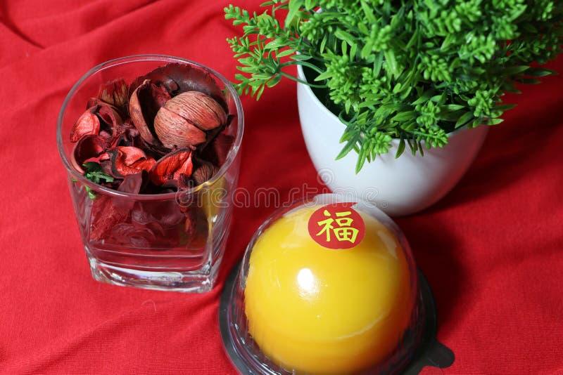 Langue chinoise : bonheur, bâton sur le gâteau orange et fleur sèche dans le verre avec la feuille verte sur le plancher rouge photographie stock