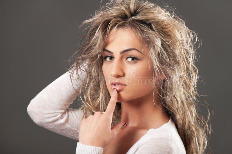 Languettes émouvantes de fille blonde attirante image stock