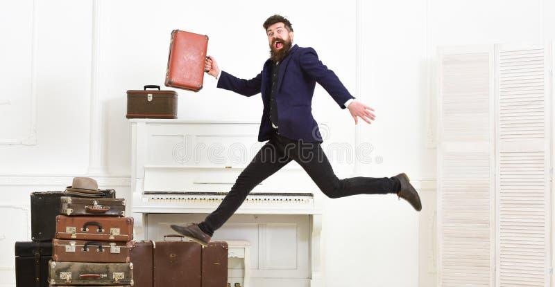 Langverwacht vakantieconcept Aantrekkelijke de macho, elegant op vrolijk gezicht draagt uitstekende koffers, het springen Mens di stock foto's