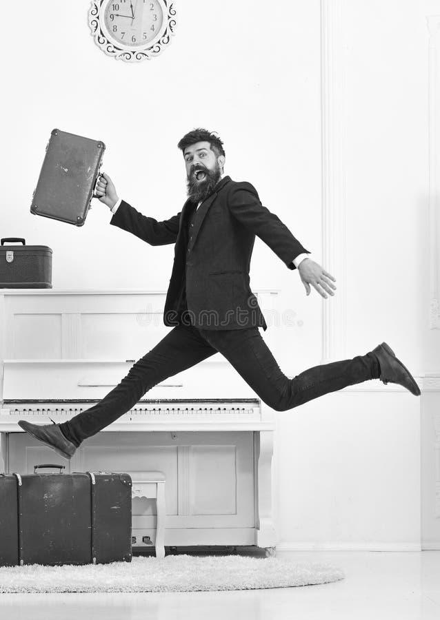 Langverwacht vakantieconcept De mens met baard en snor in kostuum draagt bagage, luxe witte binnenlandse achtergrond royalty-vrije stock foto