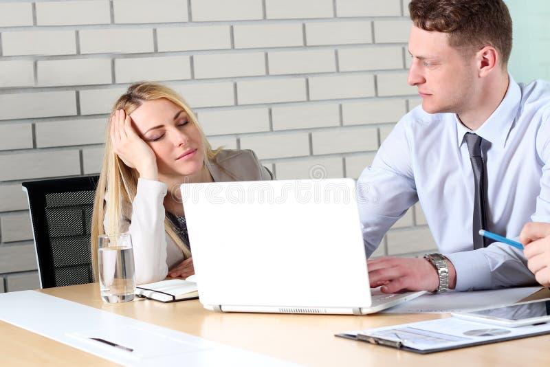 Langweilige Arbeit Junge Geschäftsleute, die beim zusammen sitzen dem Tisch und weg schauen gebohrt betrachten stockfotografie