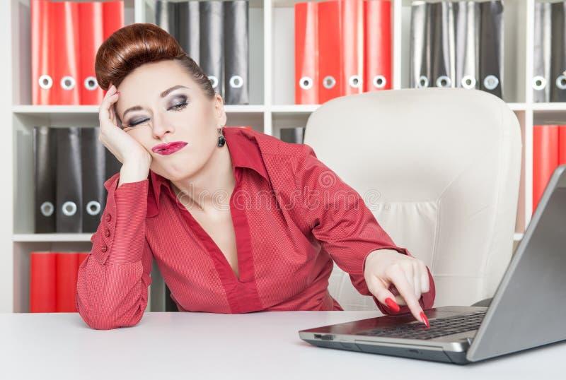 Langweilige Geschäftsfrau, die im Büro arbeitet stockfotografie