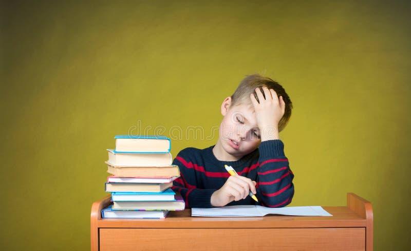 Langweilige Schulstudien heimarbeit Müdes Schreiben des kleinen Jungen Educa stockbild