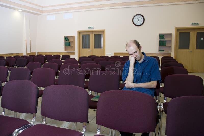 Langweiliger Vortrag. Allein schlafender Kursteilnehmer im leeren Au lizenzfreie stockfotografie