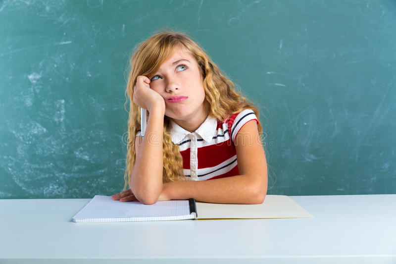 Langweiliges trauriges Ausdruckstudentenschulmädchen auf Schreibtisch lizenzfreies stockfoto