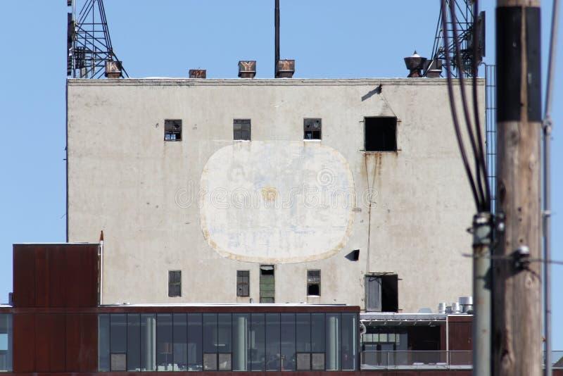Langzaam verdwenen Algemene Molensadvertentie aan de kant van een gebouw stock afbeeldingen