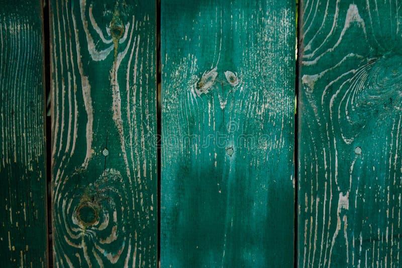 Langzaam verdwenen donkergroene oude houten planking achtergrond met barsten stock foto's