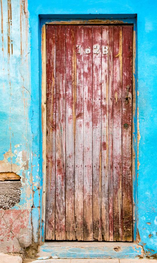 Langzaam verdwenen rode deur op blauwe bakstenen muur met gebroken pleister stock afbeelding
