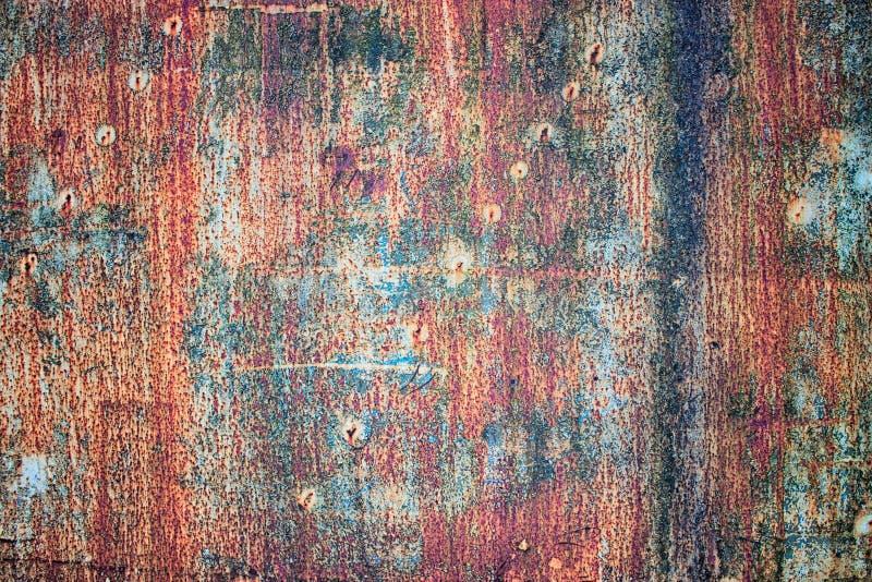 Langzaam verdwenen verf op een roestige textuur, rustieke metaalplaat stock foto's