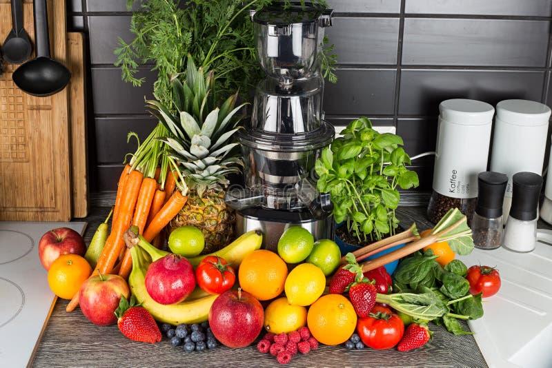 Langzame juicer in keuken met veel fruit en groentesap de gezonde achtergrond van het levensstijlconcept stock foto