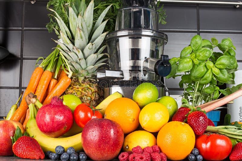 Langzame juicer in keuken met veel fruit en groentesap de gezonde achtergrond van het levensstijlconcept royalty-vrije stock afbeelding