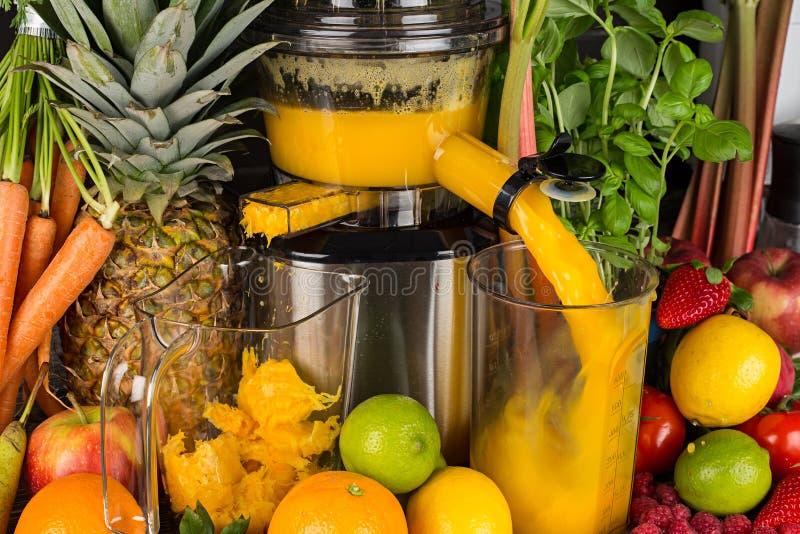 Langzame juicer in keuken met vele fruit en plantaardige oranje achtergrond van het de levensstijlconcept van het vitaminesap gez royalty-vrije stock afbeelding