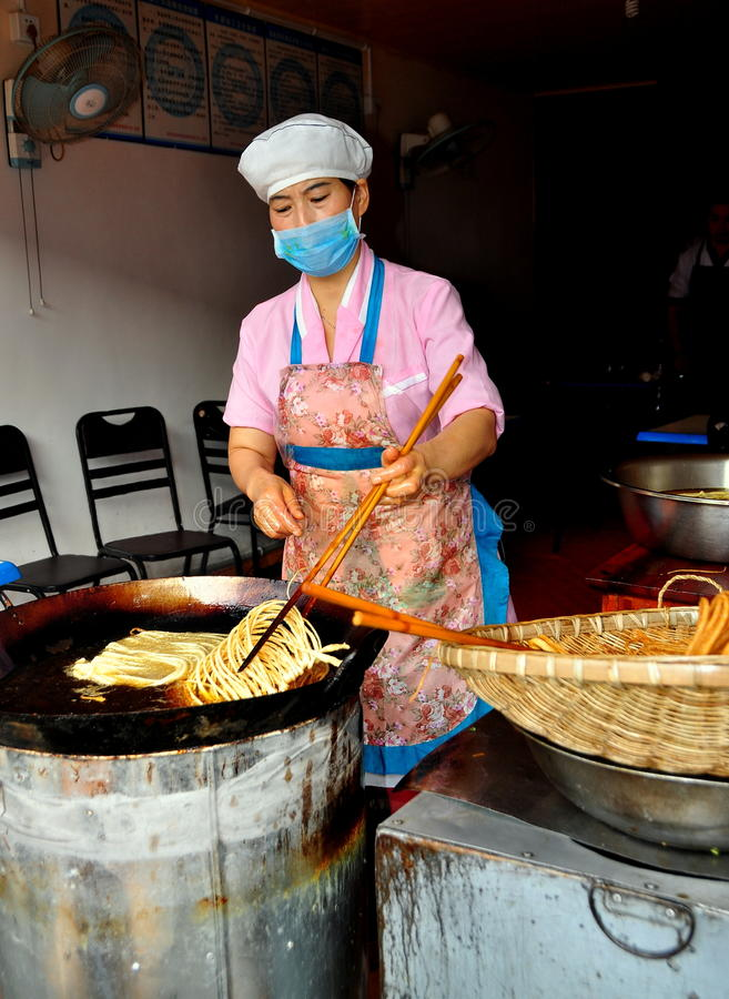 Langzhong, China: Woman Frying Noodles stock photos