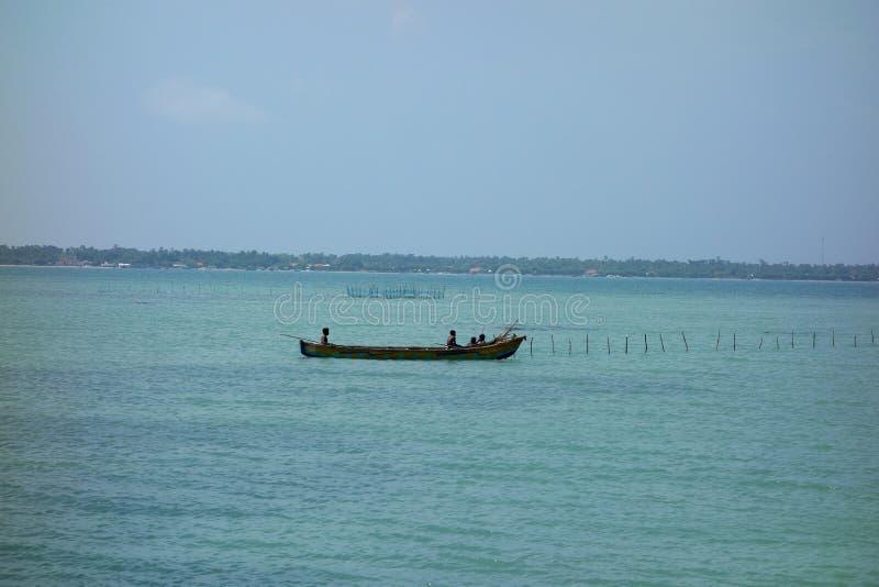 Lankijczyk wyspy chłopiec w Długim połowu czółnie fotografia stock
