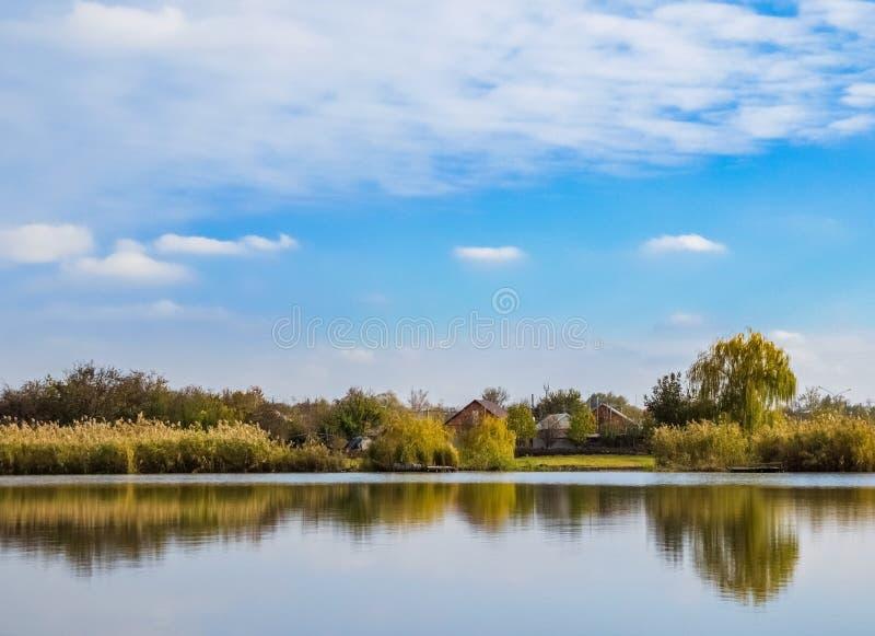 Lanscape с домами приближает к озеру под голубым небом стоковое фото rf