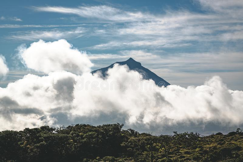 Lanscape near EN3 longitudinal road northeast of Mount Pico and the silhouette of the Mount Pico along , Pico island. Azores, Portugal. Photo taken in Azores royalty free stock images