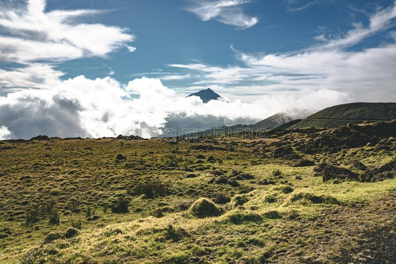 Lanscape near EN3 longitudinal road northeast of Mount Pico and the silhouette of the Mount Pico along , Pico island. Azores, Portugal. Photo taken in Azores royalty free stock photo