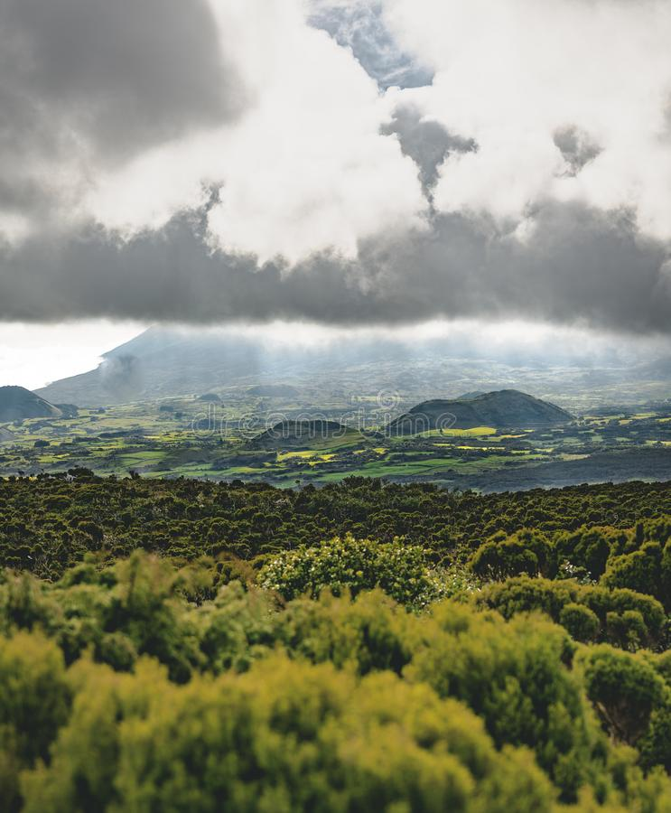 Lanscape near EN3 longitudinal road northeast of Mount Pico and the silhouette of the Mount Pico along , Pico island. Azores, Portugal. Photo taken in Azores royalty free stock photography
