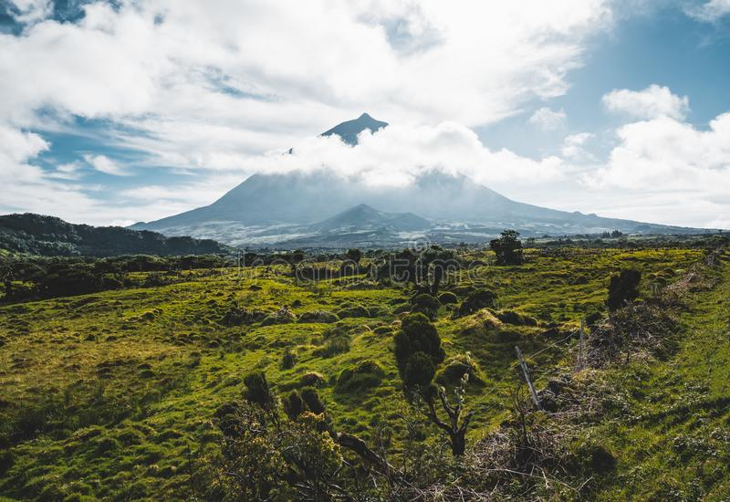 Lanscape near EN3 longitudinal road northeast of Mount Pico and the silhouette of the Mount Pico along , Pico island. Azores, Portugal. Photo taken in Azores stock photography