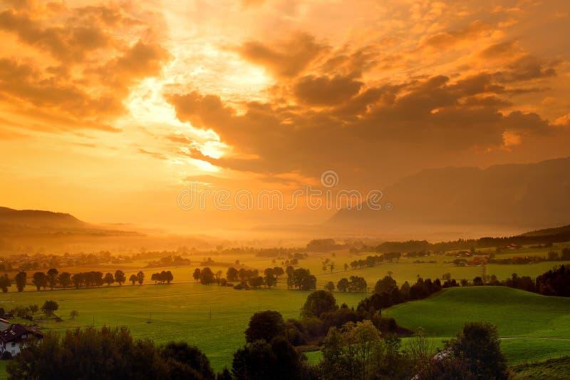 Lansdcape impresionante de la mañana del pequeño pueblo bávaro cubierto en niebla Vista escénica de las montañas bávaras en la sa fotografía de archivo libre de regalías