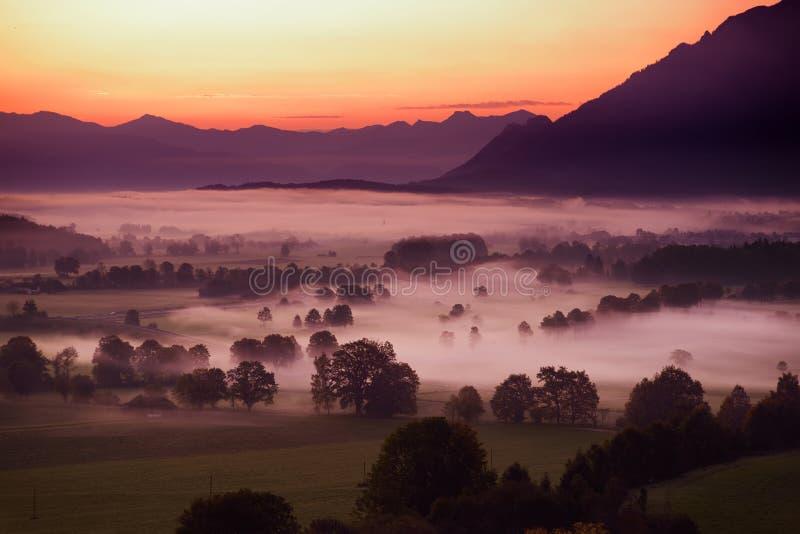 Lansdcape impresionante de la mañana del pequeño pueblo bávaro cubierto en niebla Vista escénica de las montañas bávaras en la sa imágenes de archivo libres de regalías