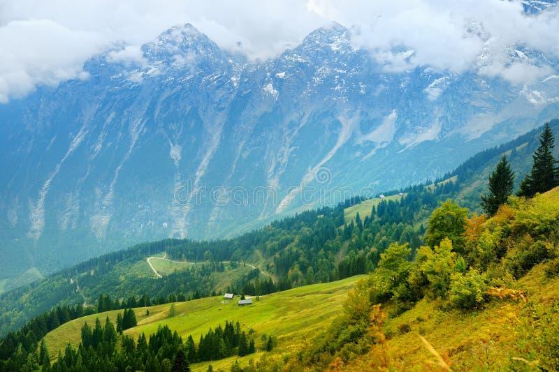 Lansdcape strabiliante delle montagne, delle foreste e di piccoli villaggi bavaresi nella distanza Vista scenica delle alpi bavar immagine stock libera da diritti